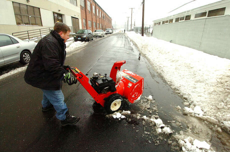 Pete Carlucci heads his snowblower down Concord Street in Norwalk after trying to locate a storm drain next to his business at Clonial Woodworking. He headed inside to grab a photo he took of its location so he can clear the snow around it to keep flooding to a minimum.