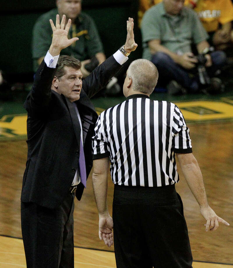 Connecticut head coach Geno Auriemma, left, argues a foul call against his team with an official during the first half of an NCAA college basketball game against Baylor Sunday, Dec. 18, 2011, in Waco, Texas. (AP Photo/Tony Gutierrez) / AP
