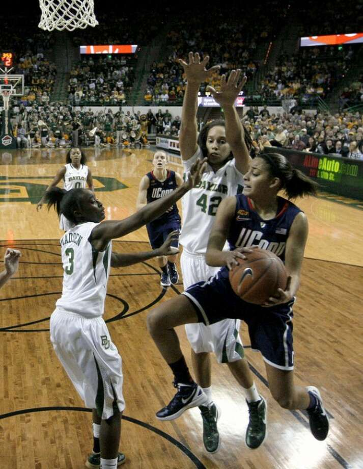 Baylor guard Jordan Madden (3) and Brittney Griner (42) combine to stop a drive to the basket by Connecticut guard Bria Hartley, front, in the first half of an NCAA college basketball game Sunday, Dec. 18, 2011, in Waco, Texas. (AP Photo/Tony Gutierrez)