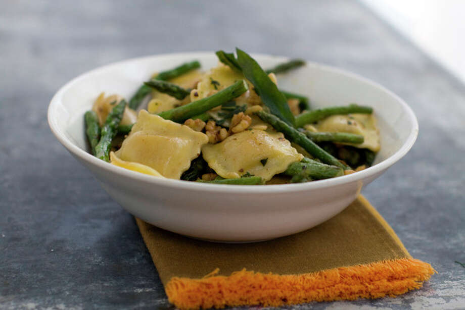 This April, 11, 2011 photo shows ravioli with fried sage, asparagus and walnuts in Concord, N.H. The asparagus and walnuts pair perfectly with the sage and ghee in this recipe, but don't hesitate to mix it up. (AP Photo/Matthew Mead) / FR170582 AP