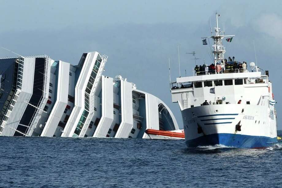 A ferry boat, right, sails past the grounded cruise ship Costa Concordia off the Tuscan island of Giglio, Italy, Sunday, Jan. 22, 2012. Rescuers on Sunday resumed searching the above-water section of the capsized Costa Concordia cruise liner, but choppy seas kept divers from exploring the submerged part, where officials have said there could be bodies. Civil protection officials said that until the waves slack off, divers would not swim into the submerged part of the vessel just off the port of Giglio, a tiny Island off the Tuscan coast. (AP Photo/Pier Paolo Cito) / AP