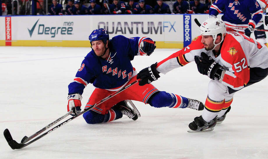 New York Rangers' Brandon Prust (8) and Florida Panthers' Jason Garrison (52) fight for control of the puck during the second period of an NHL hockey game Thursday, Jan. 5, 2012, in New York. (AP Photo/Frank Franklin II) / AP