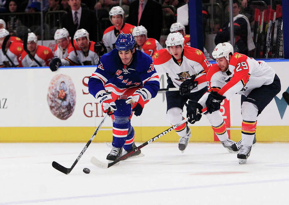 New York Rangers' Brian Boyle (22) and Florida Panthers' Bill Thomas (29) fight for control of the puck as Panthers' Mike Santorelli, center, trails the play during the second period of an NHL hockey game Thursday, Jan. 5, 2012, in New York. (AP Photo/Frank Franklin II) / AP