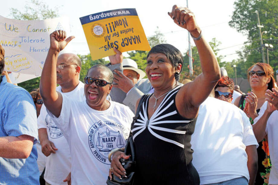 Cynthia R. Jenngings and Carroll E. Brown cheer during a speech given by Al Sharpton at a local NAACP rally in support of Tonya McDowell held at Brookside School in Norwalk Tuesday evening.