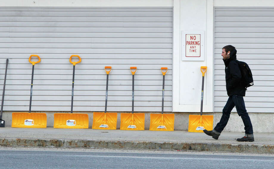 A man walks by a line of snow shovels for sale at a Reny's store, Thursday, Jan. 5, 2012, in Bridgton, Maine. Across much of the Northeast most natural snow has either melted or been washed away by rain. (AP Photo/Robert F. Bukaty) / AP