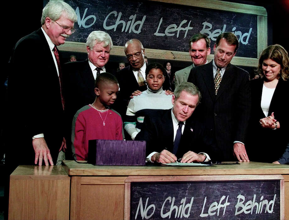 FILE - In this Jan. 8, 2002, file photo President George W. Bush, seated, signs into law a sweeping federal education bill, No Child Left Behind, at Hamilton High School in Hamilton, Ohio. Cast as a symbol of possibility, the law offered the promise of improved schools for the nation's poor and minority children and better prepared students in a competitive world. Yet after a decade on the books, Bush's most hyped domestic accomplishment has become a symbol to many of federal overreach and Congress' inability to fix something that's clearly flawed. In the image from left are Rep. George Miller, D-Calif., Sen. Edward Kennedy, D-Mass., Education Secretary Rod Paige, Sen. Judd Gregg, R-N.H., Rep. John Boehner, R-Ohio, woman at right unidentified. Children with Bush are Tez Taylor, left, and Cecilia Pallcio, right. (AP Photo/Ron Edmonds, File) / AP