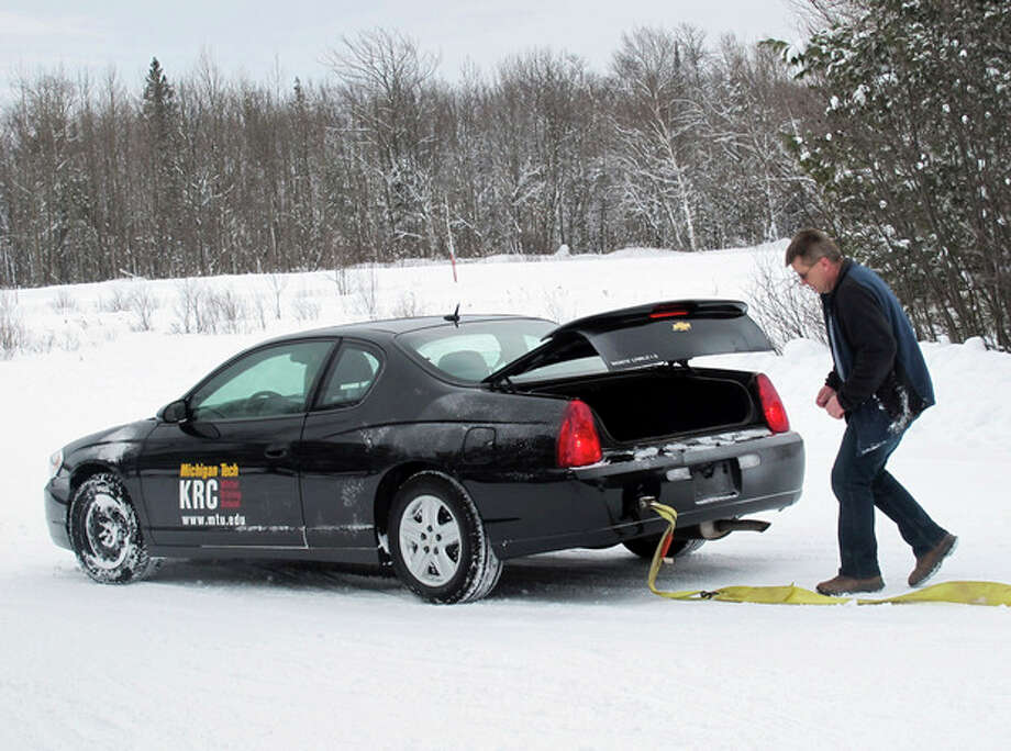 AP Photo/John Flesher In this Jan. 21, 2012 photo, photo Toby Kunnari, an instructor with the Keweenaw Research Center's winter driving school near Hancock, Mich., prepares to detach a towing line from a car that skidded into a snowbank during a training exercise. / AP