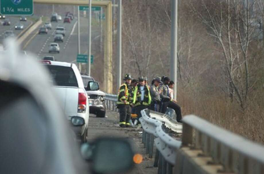 Photo/Alex von kleydorff. Emergency Personnel look over the guardrail down a 40ft embankment to where a Niassan Juke landed after bieng involved in a multi vehicle accident along the Southbound RT 7 connector