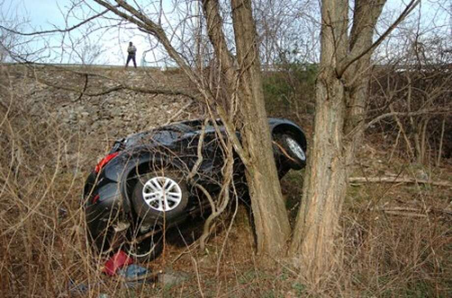 Photo/Alex von Kleydorff A Nissan Juke lies at the bottom of a 40ft embankment after being involved in a multi car accident and rolling into a tree off the RT 7 Connector southbound on Monday afternoon