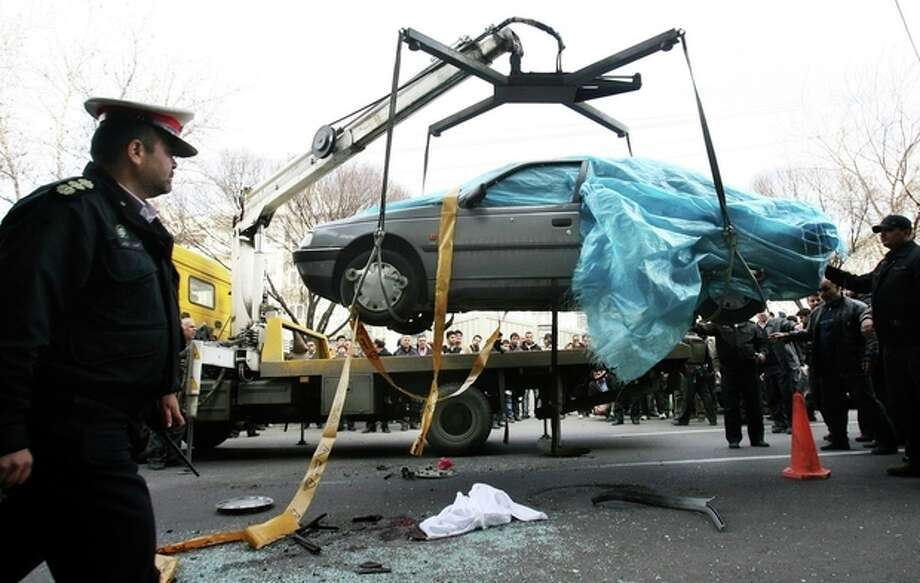 In this photo provided by the semi-official Fars News Agency, people gather around a car as it is removed by a mobile crane in Tehran, Iran, Wednesday, Jan. 11, 2012. Two assailants on a motorcycle attached magnetic bombs to the car of an Iranian university professor working at a key nuclear facility, killing him and wounding two people on Wednesday, a semiofficial news agency reported. (AP Photo/Fars News Agency, Meghdad Madadi) / Fars News Agency