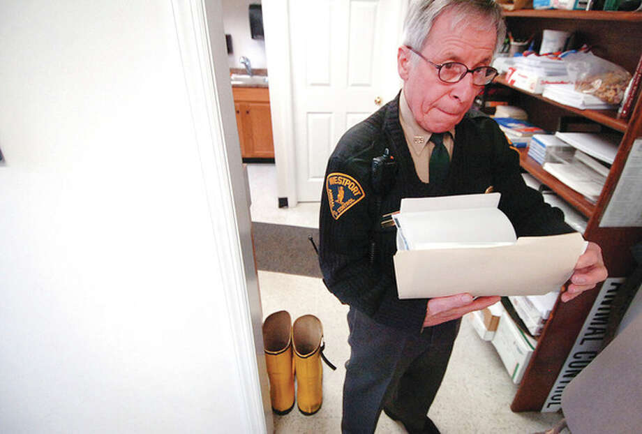 Hour Photo/ Alex von Kleydorff. Westport Animal Control Officer Peter D'Amico looks through a folder containing photos of some of the animal cases he has worked on. / © 2012 The Hour Newspapers