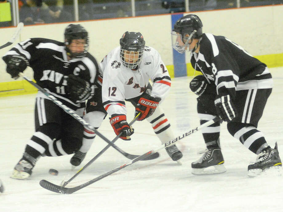 Hour photo/Matthew Vinci New Canaan's Danny Newman tries to force his way past Xavier defenders Dan Dupont, left, and Dakota Caron during Monday's game at Darien Ice Rink. hjkhljk / (C)2011, The Hour Newspapers, all rights reserved