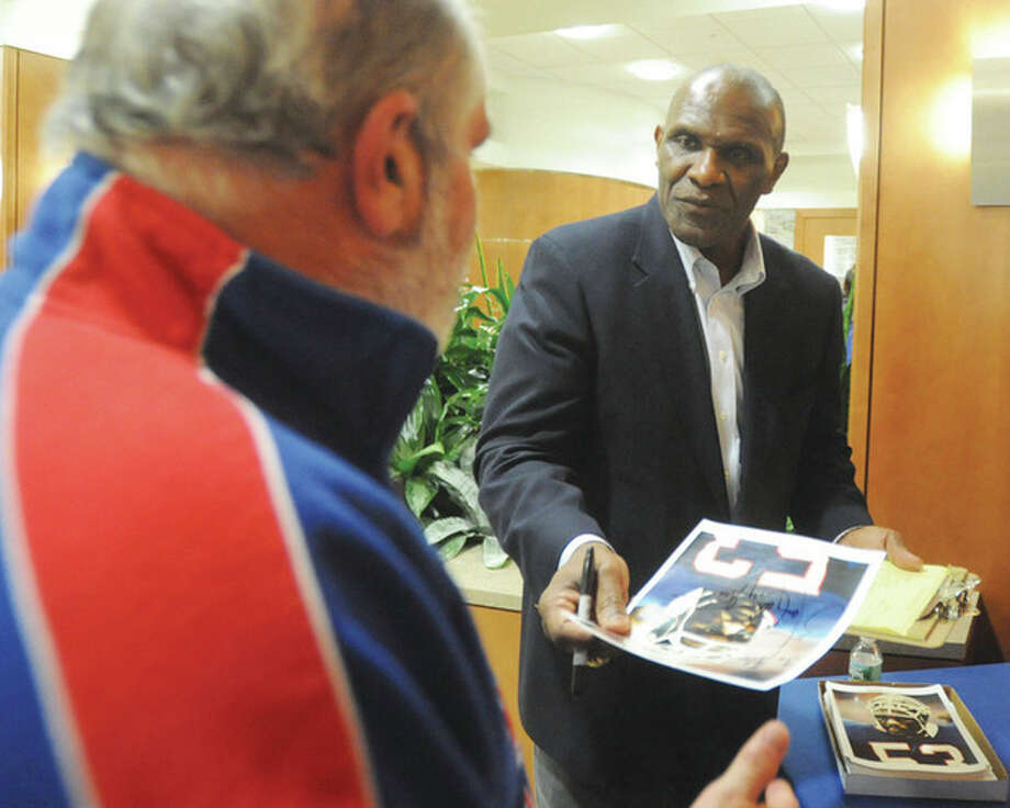 Hour photo/John Nash Former New York Giants linebacker Harry Carson, right, hands an autographed photo to Glenn Landry of Bridgeport during an appearance at Norwalk Hospital on Wednesday night. The Hall of Famer was on hand to talk about prostate cancer awareness, but took time out to say that he liked his old team's chances in Sunday's NFC championship game against the San Francisco 49ers.