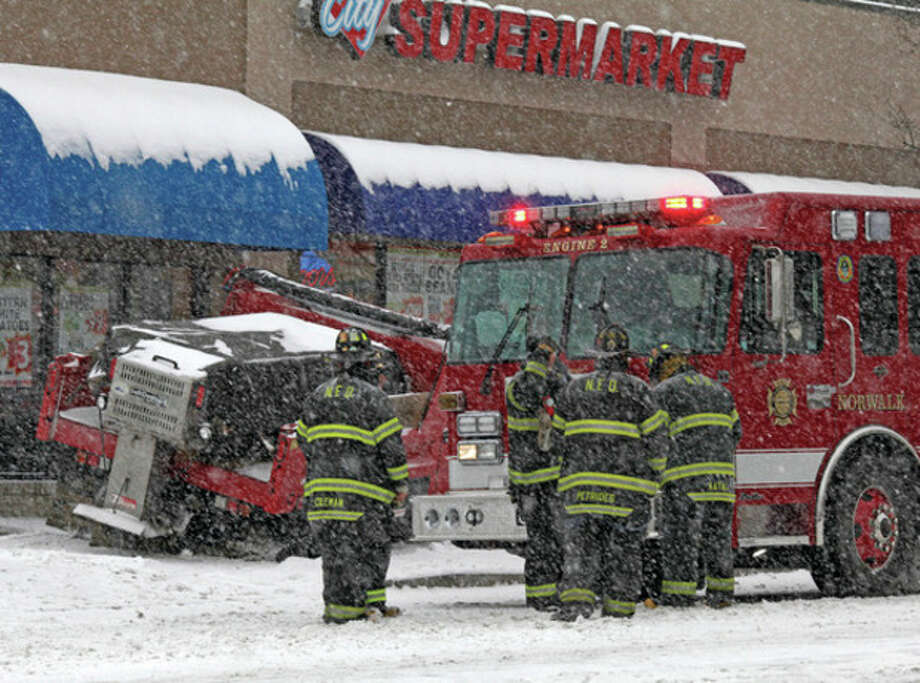 Firefighters respond to an accident that happened just outside of City Market on West Avenue in Norwalk Saturday morning during the snow storm. Hour Photo / Danielle Robinson