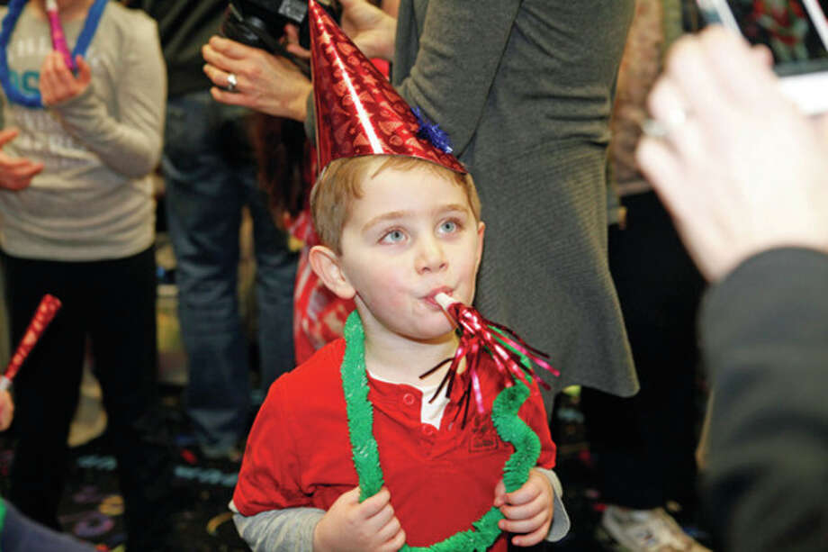 "Artie Cummins, 5, blows into his noise maker as the clock strikes 12 during Pump It Up's ""Noon Years Eve"" Party Saturday morning in Norwalk. Hour Photo / Danielle Robinson"