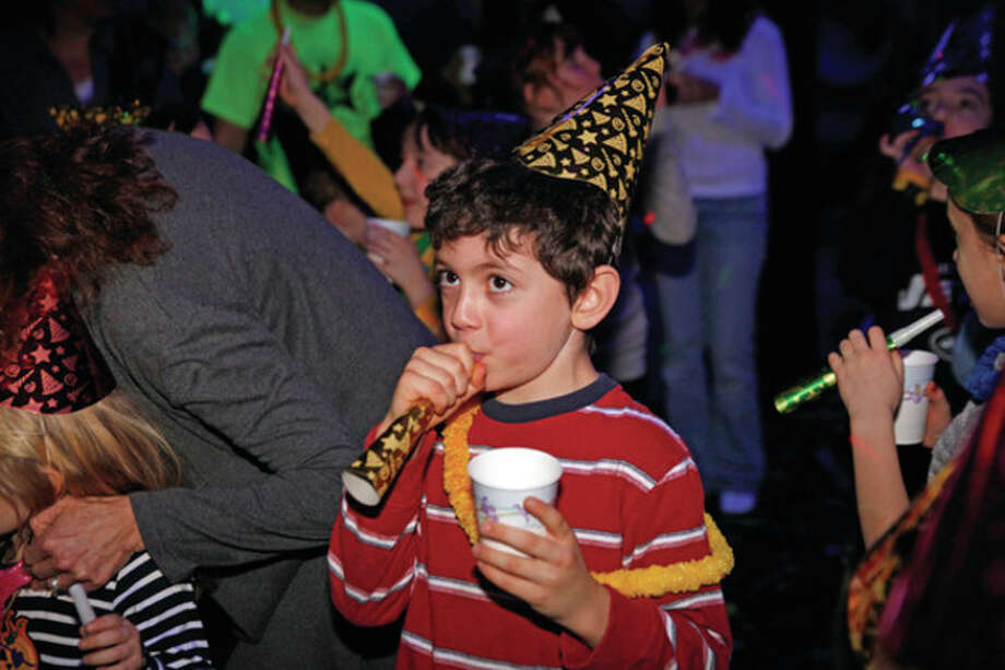 """James Toomey, 7, blows into his noise maker as the clock strikes 12 during Pump It Up's """"Noon Years Eve"""" Party Saturday morning in Norwalk. Hour Photo / Danielle Robinson"""