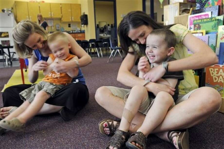 In this May 11, 2011 photo, Jackie Johnson with her son Ben, 3, left, and Anita Sonnek with her son Owen, 3, play during an Early Childhood Family Education program activity in Waconia, Minn. The district''s elementary schools are so packed, they had to create space in one of the district warehouses for early childhood classes, (AP Photo/Craig Lassig)