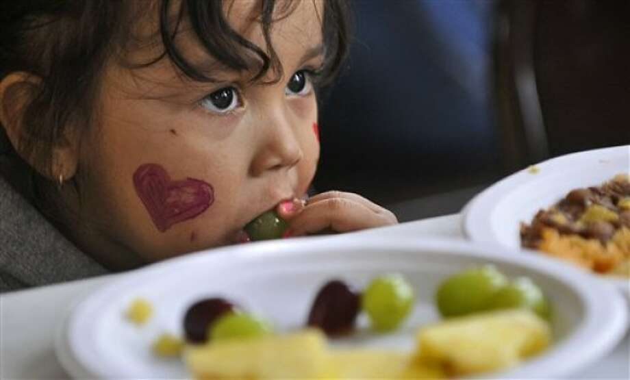 In this April 10, 2011, photo, Alexis Borja, 2, samples Latino-style food at St. Boniface Catholic Church in Cold Spring, Minn., during Dia de la Identidad (Identity Day), which included a Spanish-language Mass, a photography exhibit, food, pinatas, and music by a Latino group from the College of St. Benedict/St. John''s University. Cold Spring, home of a Gold''n Plump poultry plant, had 40 Hispanic residents a decade ago and now has 287, according to the census bureau. Sauk Centre''s Hispanic residents increased by 800 percent from 21 to 189. Elsewhere in Central Minnesota, the cities of Long Prairie and Willmar also experienced burgeoning Hispanic populations. (AP Photo/St. Cloud Times, Kimm Anderson)