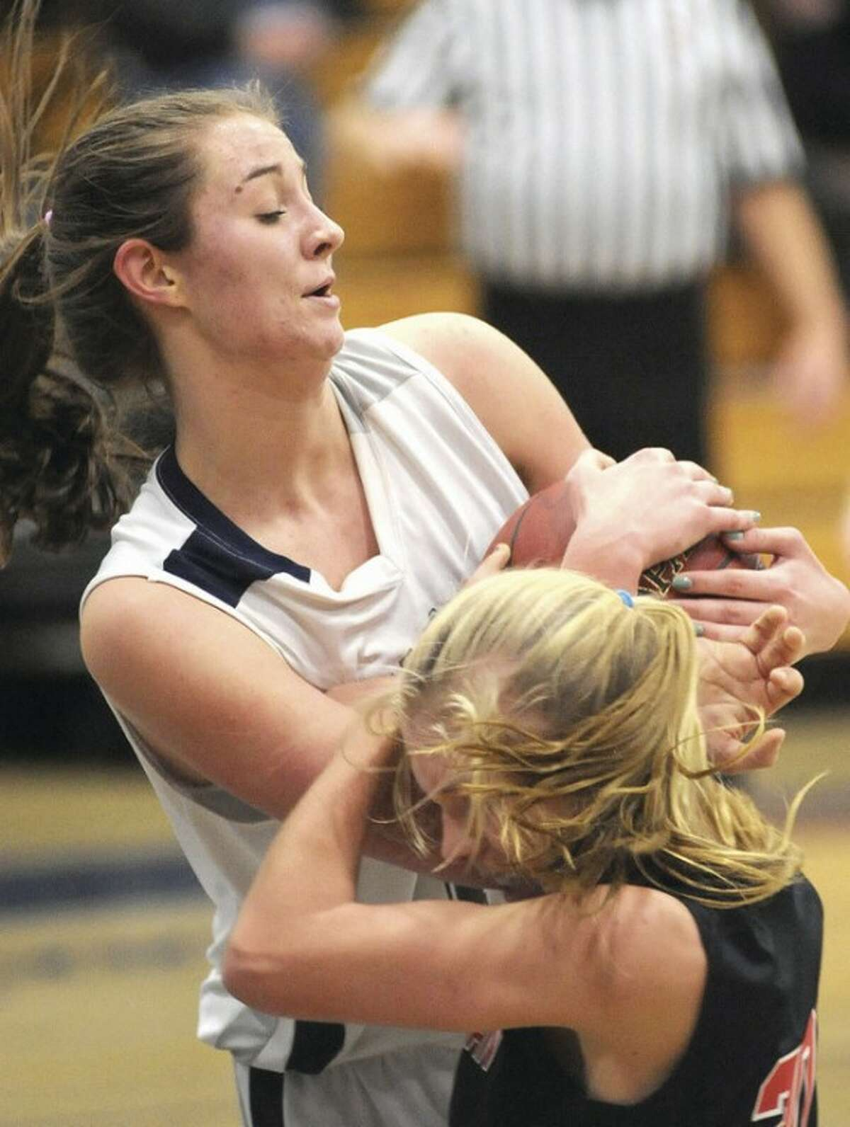Hour photo/John Nash Staples center Jess Coelho gets tied up by New Canaan's Kelly Armstrong during the third quarter of Thursday's FCIAC game in Westport. Coelho and the Wreckers handed the visiting Rams a 62-56 defeat.