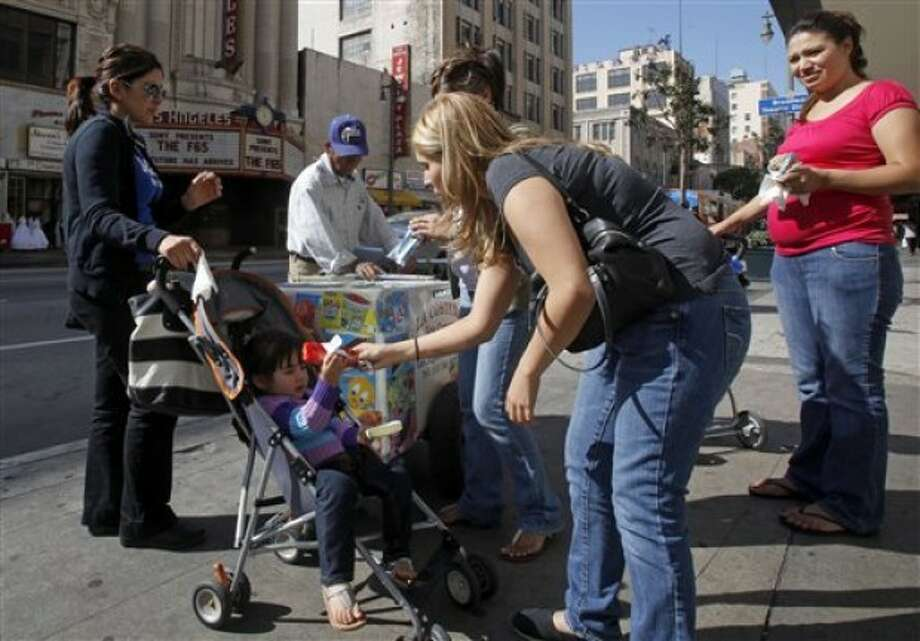 Latinos buy ice cream from a sidewalk vendor, across from the Los Angeles Theater on Broadway in downtown Los Angeles, where many businesses cater to a Spanish-speaking clientele, Wednesday, May 11, 2011. According to Census Bureau figures to be released Thursday, May 12, the population of people of Mexican descent in California grew by 6 percent in the last decade, and represent 31 percent of the total in the state. (AP Photo/Reed Saxon)