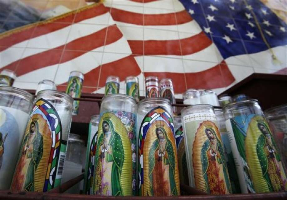Votive candles at a shrine to the Virgin of Guadalupe, the patron saint of Mexico, stand before a portion of a mosaic that features the U.S. flag, at the Old Plaza Church (La Placita), the site of the first settlement of the city by emigrants from Mexico, in Los Angeles'' Olvera Street area Wednesday, May 11, 2011. According to Census Bureau figures to be released Thursday, May 12, the population of persons of Mexican origin in California grew by 6 percent in the last decade, and represent 31 percent of the total in the state. (AP Photo/Reed Saxon)