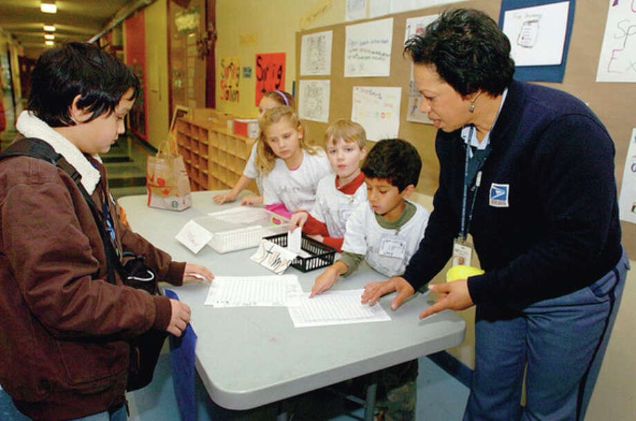 Hour photo / Erik Trautmann U.S. Postal Service letter carrier Emma Lawson, right, helps Columbus Magnet School second-graders Emily Seneck , Jordan Longo, Darren Forschino and Jay Sharma give stamps and stationary to fifth-grader Benjamin Russo after he donated canned food to the school's Speedy Postal Service program Wednesday to help with the school's food drive. / (C)2011, The Hour Newspapers, all rights reserved
