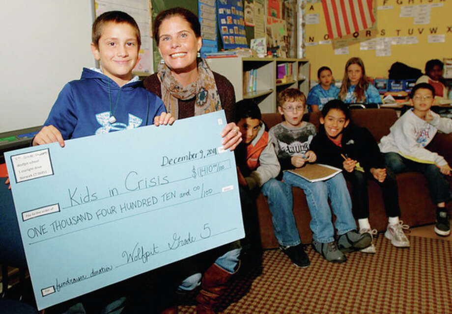 "Hour photo / Erik Trautmann Wolfpit Elementary School fifth-grader Samuel White presents ""Kids in Crisis"" Managing Director of Development Mary Vinton with more than $1,400 the fifth-grade raised with their talent show and concession. / (C)2011, The Hour Newspapers, all rights reserved"
