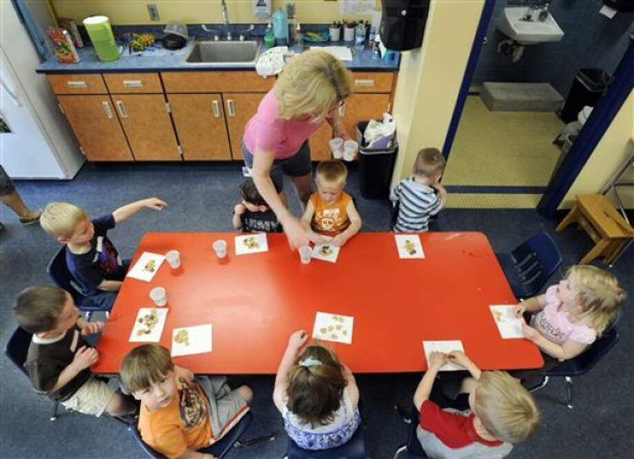 In this May 11, 2011 photo, teacher Kristie Niebeling hands out snacks to children during an Early Childhood Family Education program in Waconia, Minn. The district''s elementary schools are so packed, they had to create space in one of the district warehouses for early childhood classes. (AP Photo/Craig Lassig)