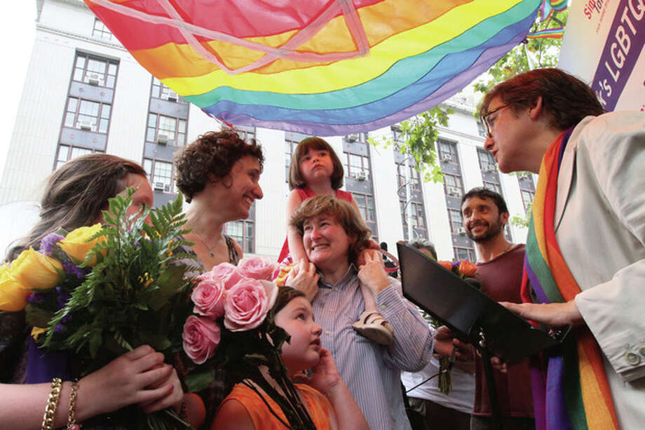 Under a rainbow chuppah, Rabbi Sharon Kleinbaum, senior rabbi at Congregation Beit Simchat Torah Synagogue in New York, right, marry Sari Kessler, second from left, and Erika Karp, center, as their three daughters and Kessler's brother, Jonathan Kessler, second from right, surround them Sunday July 24, 2011, in a park across the street from the Office of the City Clerk in New York. The couple, who live in New York, have been together for 14 years. Hundreds of gay couples were expected to marry in New York and across the Empire State on the first day of same-sex marriage ceremonies. (AP Photo/Tina Fineberg) / FR73987 AP