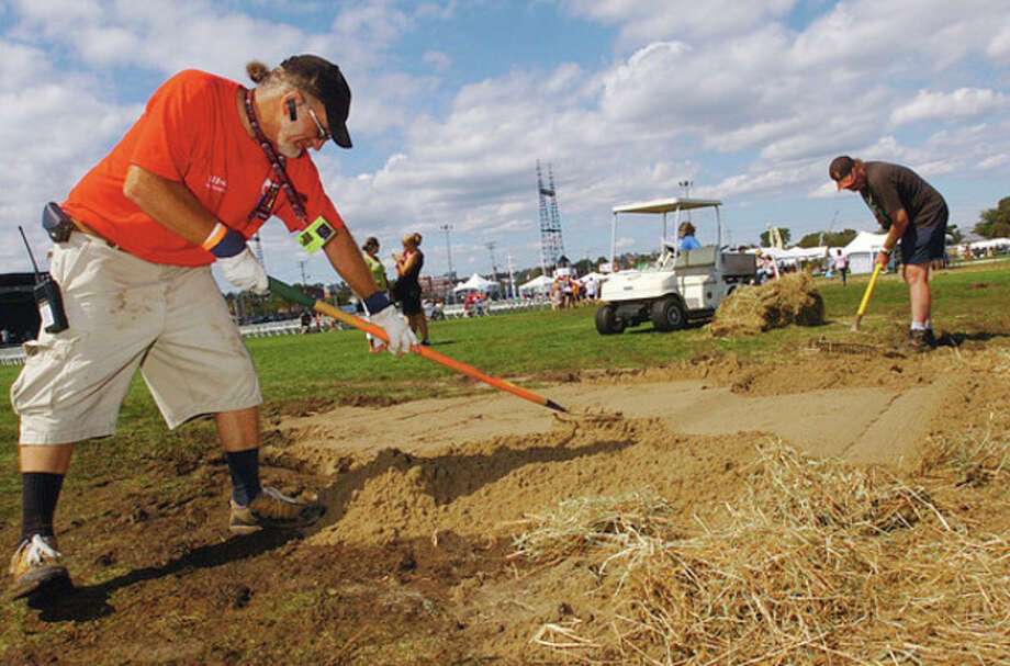 Volunteers Bob Sodaro and Greg Hunter rack out sand and hay to cover areas of mud at the 2011 Norwalk Seaport Association Oyster Festival Saturday at Veteran's Memorial Park. / (C)2011, The Hour Newspapers, all rights reserved