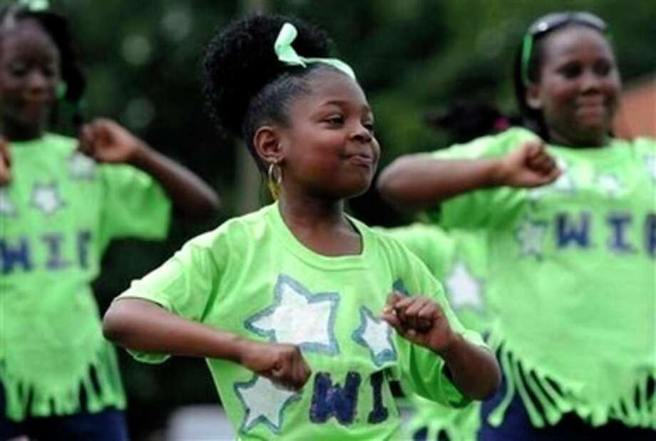 Keiana Welsh dances with the West Indian Foundation Summer Enrichment Program before the annual West Indian parade, in Hartford, Conn., Saturday, Aug. 13, 2011. Parade organizers say encouragement from city officials and a desire to accommodate the growing Caribbean population led to the decision to bring Saturday's parade into Bushnell Park. (AP Photo/Jessica Hill) / AP2011