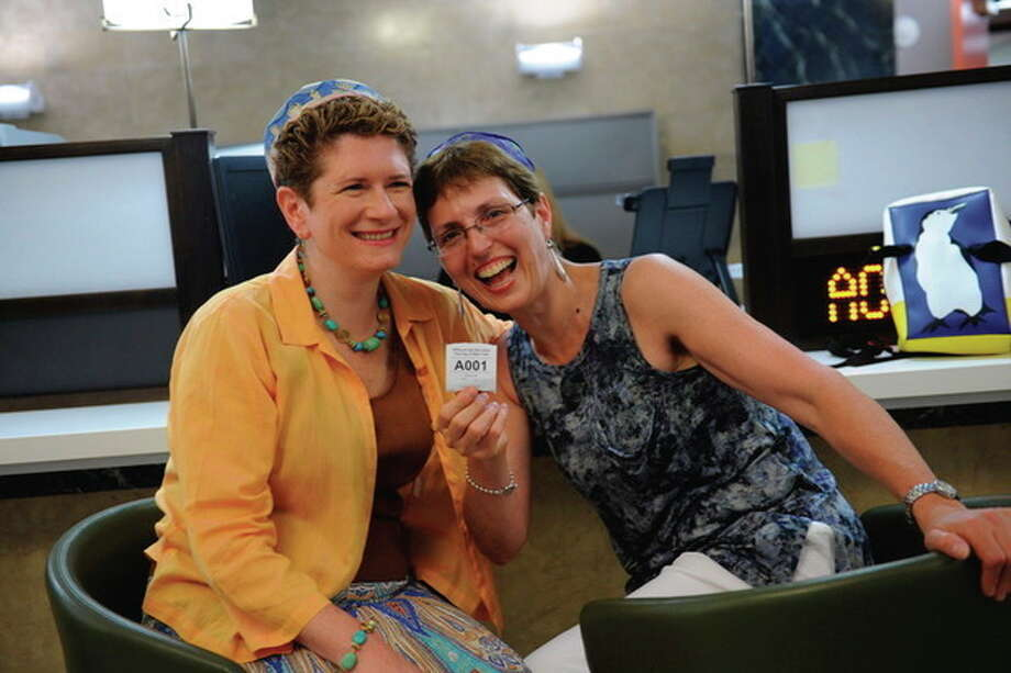Nancy Mertzel, left and Yolanda Potasinski display the ticket for their wedding ceremony at the City Clerk's Office in New York Sunday, July 24, 2011. Hundreds of gay couples were expected to marry in New York and across the Empire State on the first day of same-sex marriage ceremonies. (AP Photo/David Handschuh, Pool) / Pool New York Daily News