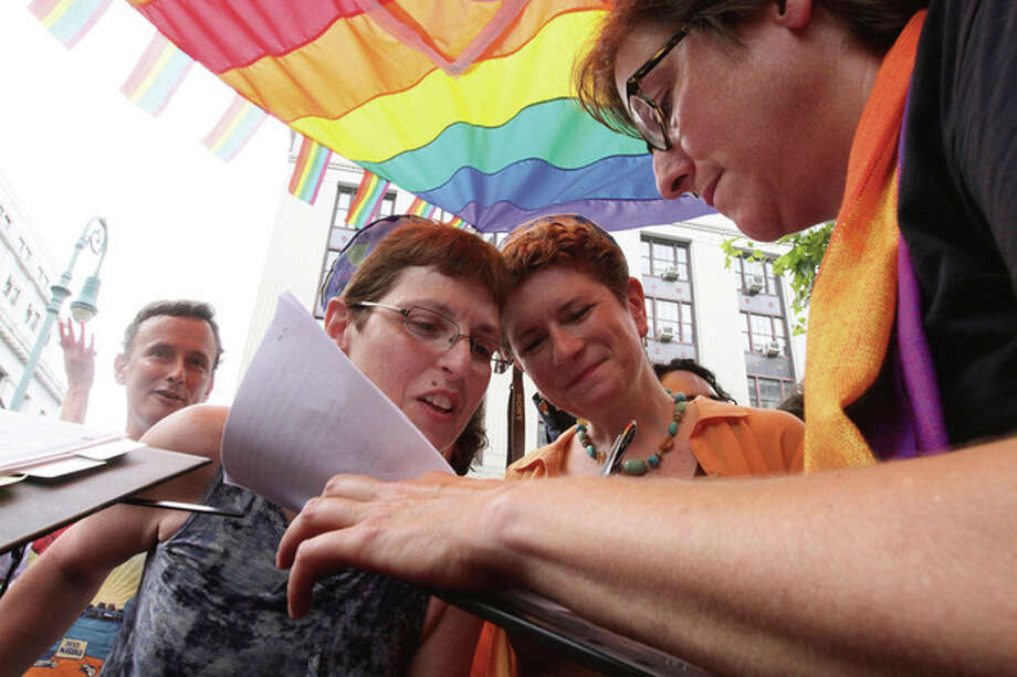 Under a rainbow chuppah, Rabbi Sharon Kleinbaum, right, senior rabbi at Congregation Beit Simchat Torah Synagogue in New York, marries Yolanda Potasinski, foreground left, and Nancy Mertzel, second from right, Sunday July 24, 2011, in a park across the street from the Office of the City Clerk in New York. The couple, who live in New York, have been together for 17 years. (AP Photo/Tina Fineberg) / FR73987 AP