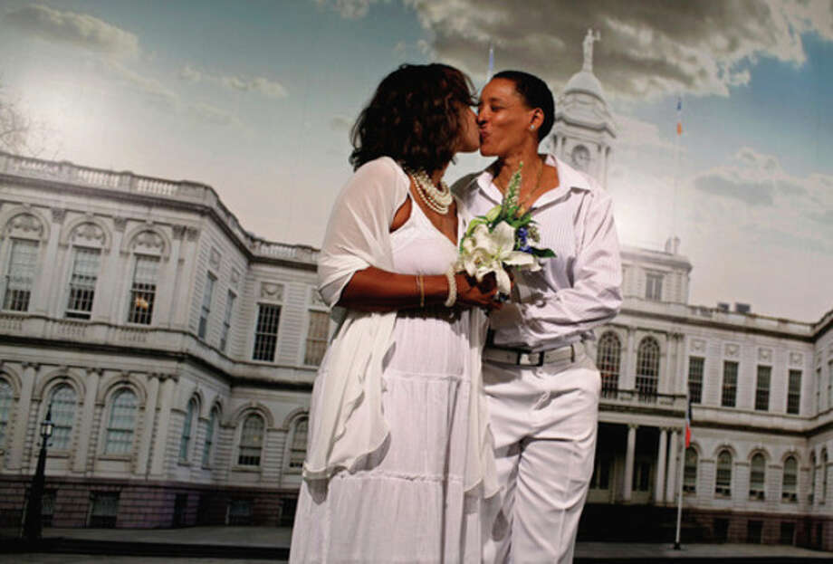 Rhonda Otten, left and Debra Curtis of Montclair, N.J. kiss in front of a backdrop of New York's City Hall before their marriage ceremony at the City Clerk's office in New York Sunday, July 24, 2011. Hundreds of gay couples were expected to marry in New York and across the Empire State on the first day same-sex marriage ceremonies. (AP Photo/Craig Ruttle) / FR61802 AP