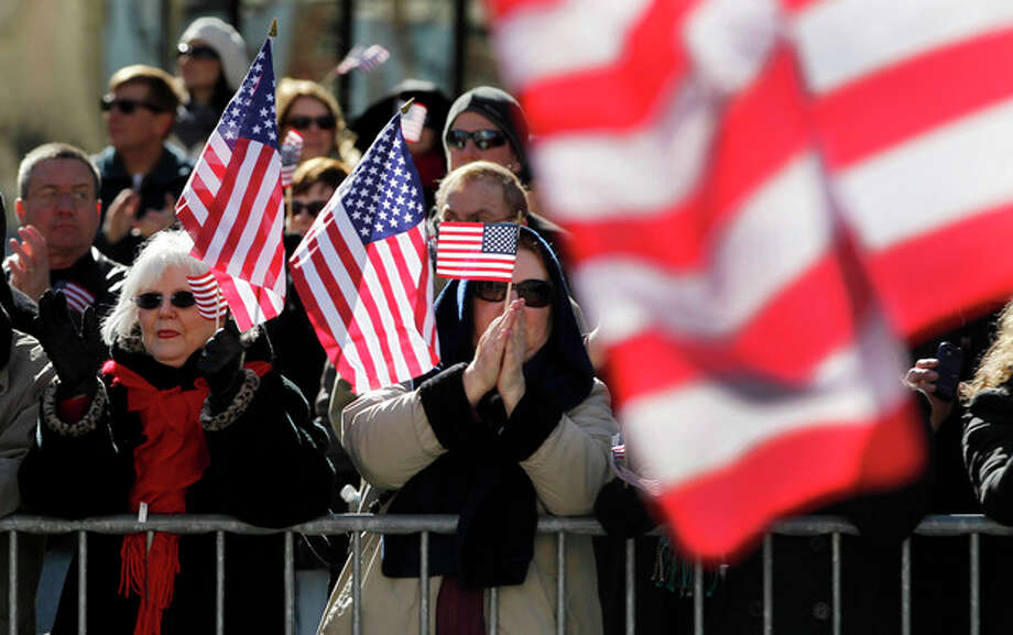 Spectators applaud as a parade to honor Iraq War veterans passes Saturday, Jan. 28, 2012, in St. Louis. Thousands turned out to watch the first big welcome home parade in the U.S. since the last troops left Iraq in December. (AP Photo/Jeff Roberson) / AP
