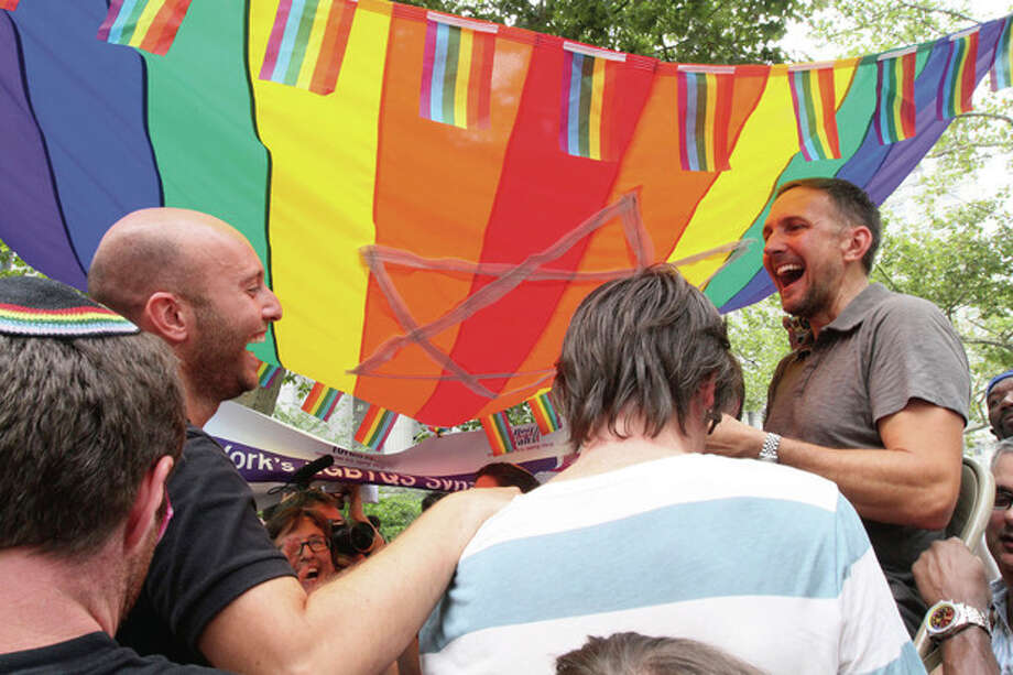 Under a rainbow chuppah, Guy Rozenstrich, second from left, and Stephen Hoerz, right, are raised on chairs as they celebrate after their marriage performed by Rabbi Sharon Kleinman, third from left wearing glasses, senior rabbi at Congregation Beit Simchat Torah Synagogue in New York, Sunday July 24, 2011 in a park across the street from the Office of the City Clerk in New York. The couple, who live in New York, have been together for 8 years. Hundreds of gay couples were expected to marry in New York and across the Empire State on the first day of same-sex marriage ceremonies. (AP Photo/Tina Fineberg) / FR73987 AP
