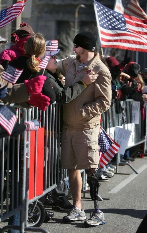 George Fernau, left, from Florissant, Mo., gives a hug to Iraq war vet Bobby Lisek, from Clever, Mo., as he marches along Market Street Saturday, Jan. 28, 2012 in St. Louis. Lisek, a former sergeant in the Army, was wounded in a IED attack in Baghdad on September 11, 2004. (AP Photo/St. Louis Post-Dispatch, David Carson) EDWARDSVILLE INTELLIGENCER OUT; THE ALTON TELEGRAPH OUT