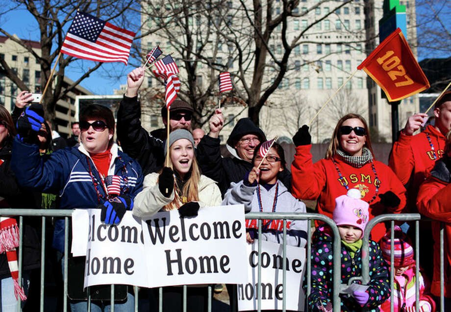 Spectators cheer and wave as they watch a parade to honor Iraq War veterans pass Saturday, Jan. 28, 2012, in St. Louis. Thousands turned out to watch the first big welcome home parade in the U.S. since the last troops left Iraq in December. (AP Photo/Jeff Roberson) / AP