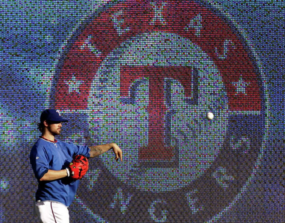 Texas Rangers' C.J. Wilson tosses the ball during afternoon practice with the team Monday, Oct. 17, 2011, in Arlington, Texas. The Rangers and the St. Louis Cardinals are scheduled to play the opening game of baseball's World Series on Wednesday in St. Louis. (AP Photo/Tony Gutierrez) / AP