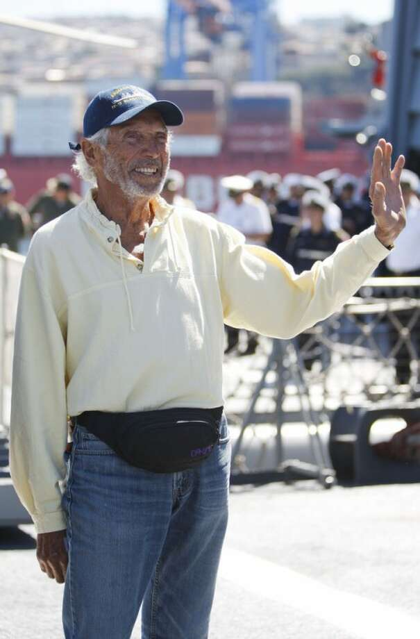 U.S. sailor Thomas Louis Corogin waves to reporters after arriving at the port of Valparaiso, Chile, Monday, Jan. 9, 2012. The 84-year-old American who put out an emergency distress signal on Jan. 2, 2012 after cracks in his mast made it impossible for him to raise his sails, is in good condition. Chile's navy rerouted a Japanese merchant ship to his location. (AP Photo/Roberto Candia)