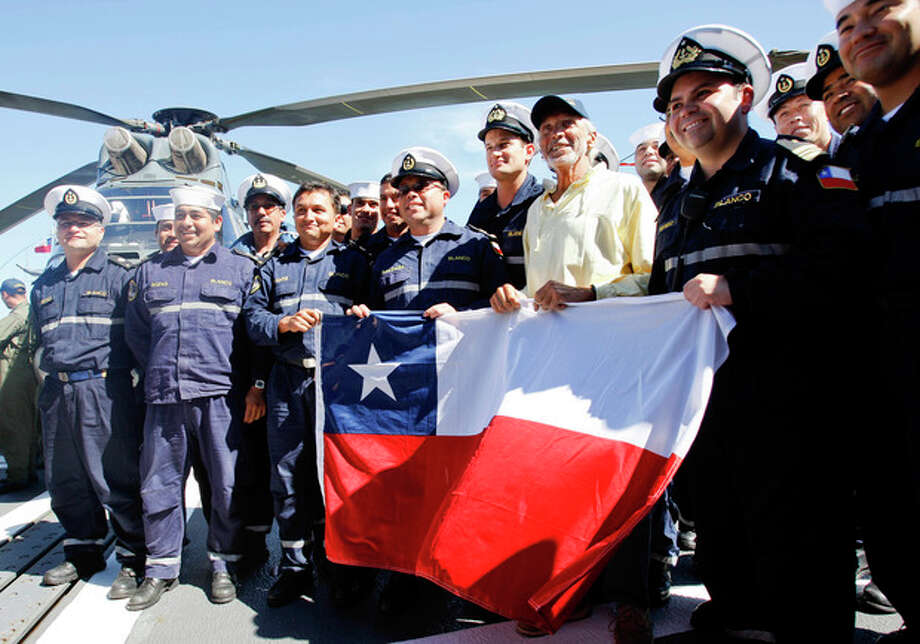 U.S. sailor Thomas Louis Corogin, in yellow, holds a Chilean flag surrounded by Chile's Navy officers after arriving to the port of Valparaiso, Chile, Monday, Jan. 9, 2012. The 84-year-old American who put out an emergency distress signal on Jan. 2, 2012 after cracks in his mast made it impossible for him to raise his sails, is in good condition. Chile's navy rerouted a Japanese merchant ship to his location. (AP Photo/Roberto Candia) / AP