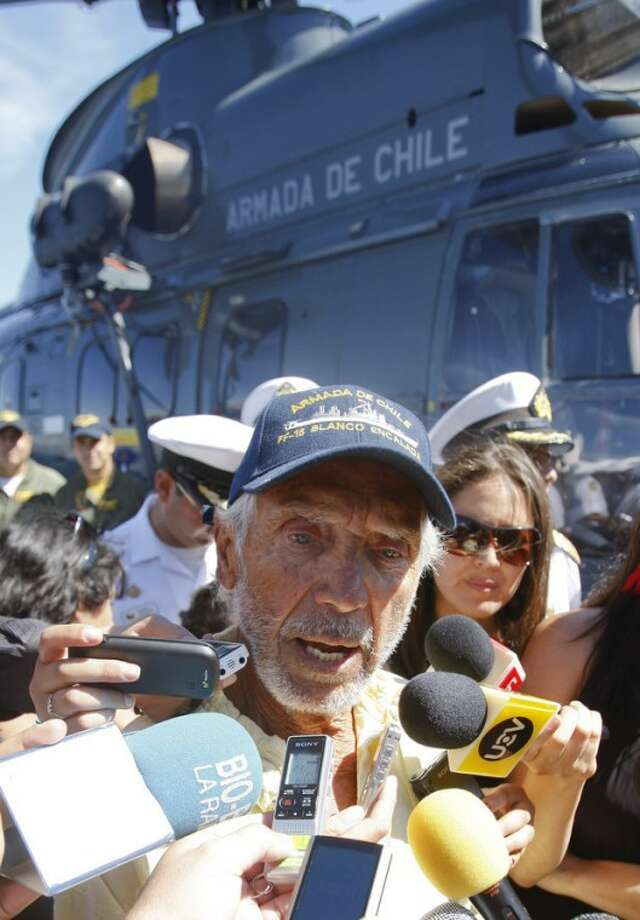 U.S. sailor Thomas Louis Corogin, center, speaks to reporters after arriving to the port of Valparaiso, Chile, Monday, Jan. 9, 2012. The 84-year-old American who put out an emergency distress signal after cracks in his mast made it impossible for him to raise his sails, is in good condition. Chile's navy rerouted a Japanese merchant ship to his location. (AP Photo/Roberto Candia)