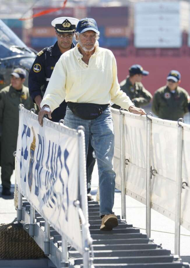 U.S. sailor Thomas Louis Corogin, front, walks down Chile's Navy ship Blanca Encalada upon his arrival to the port of Valparaiso, Chile, Monday, Jan. 9, 2012. The 84-year-old American who put out an emergency distress signal on Jan. 2, 2012 after cracks in his mast made it impossible for him to raise his sails, is in good condition. Chile's navy rerouted a Japanese merchant ship to his location. (AP Photo/Roberto Candia)