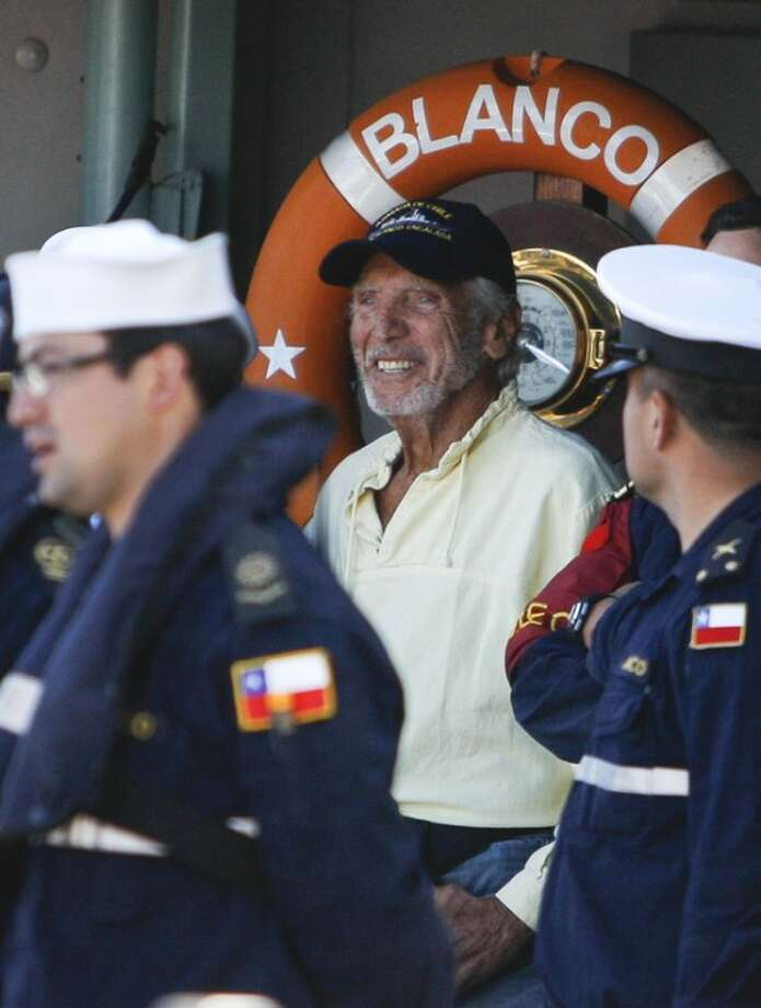 U.S. sailor Thomas Louis Corogin, center, gestures aboard Chile's Navy ship Blanco Encalada at the port of Valparaiso, Chile, Monday, Jan. 9, 2012. The 84-year-old American who put out an emergency distress signal on Jan. 2, 2012 after cracks in his mast made it impossible for him to raise his sails, is in good condition. Chile's navy rerouted a Japanese merchant ship to his location. (AP Photo/Roberto Candia)