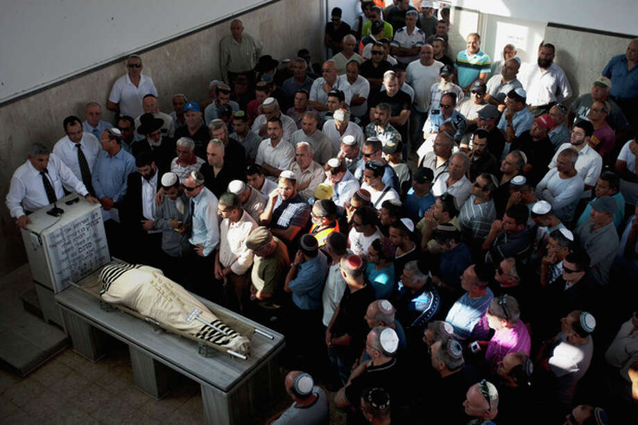 Family and friends of Ami Moshe gather next to his body during his funeral procession in Ashkelon, southern Israel, Sunday, Oct. 30, 2011. Moshe was killed after a rocket fired by Palestinians militants from Gaza Strip hit the town of Ashkelon on Saturday night. On Saturday, nine militants and an Israeli civilian were killed in some of the worst violence in the area in months. (AP Photo/Ariel Schalit) / AP