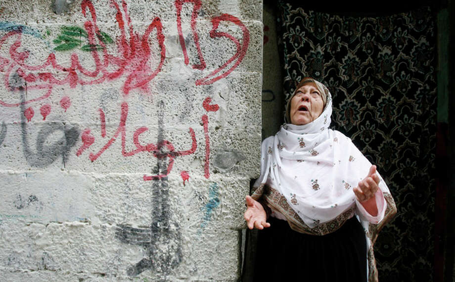 """A Palestinian woman reacts during the funeral of Ismalic Jihad militant of Ahmed al-Sheikh Khalil and other two militants, in Rafah, southern Gaza Strip, Sunday, Oct. 30, 2011. Nine militants and an Israeli civilian were killed in some of the worst violence in the area in months. The exchange of fire continued overnight, with Palestinians firing 10 rockets into Israel in the early hours of the morning, and Israeli aircraft targeting six militant sites in Gaza, the military said. Arabic on wall reads: """"House for sale, Abu Ala"""". (AP Photo/Eyad Baba) / AP"""