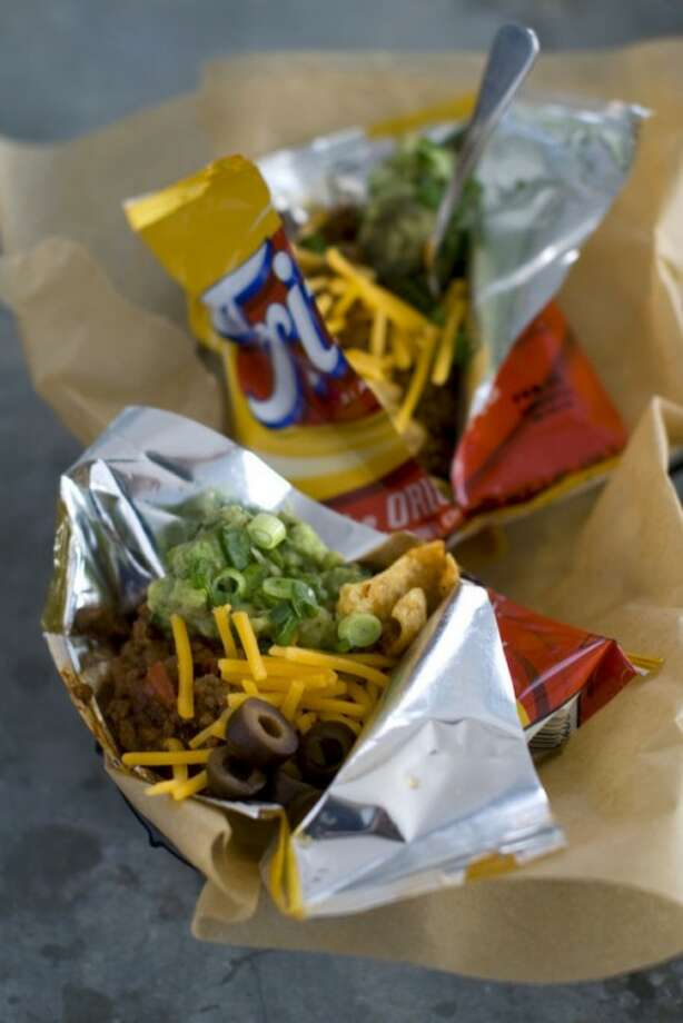 This Jan. 4, 2012 photo shows Elizabeth Karmel's recipe for a walking taco in Concord, N.H. A walking taco is a variety of toppings dumped into a snack-size bag of Fritos and eaten right from the bag. (AP Photo/Matthew Mead)