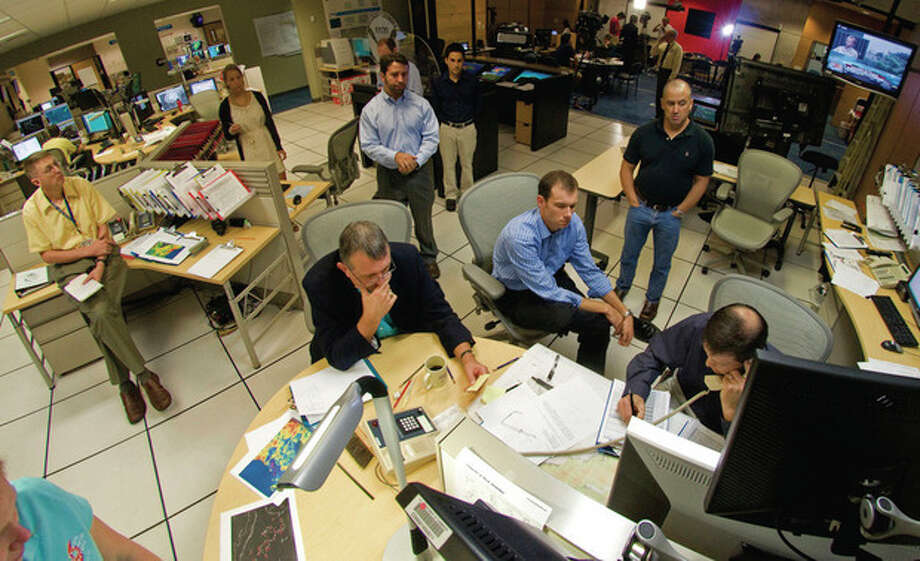 Personnel at the National Hurricane Center in Miami, including NHC director Bill Read, center bottom, conduct a conference call to coordinate the 11 a.m. ET forecast for Hurricane Irene, Saturday, Aug. 27, 2011. (AP Photo/Andy Newman) / AP