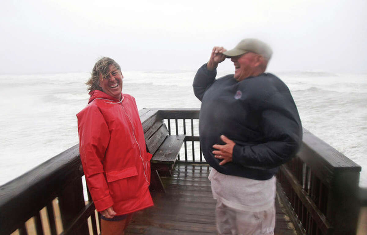 Defying mandatory evacuation orders and a curfew, summer residents Pam Cooke, left, and Jody Bowers share a laugh as strong winds puff up Jody's jacket as they venture out to the beach in Kill Devil Hills, Outer Banks, N.C., Saturday, Aug. 27, 2011 as Hurricane Irene reaches the North Carolina coast. (AP Photo/Charles Dharapak)