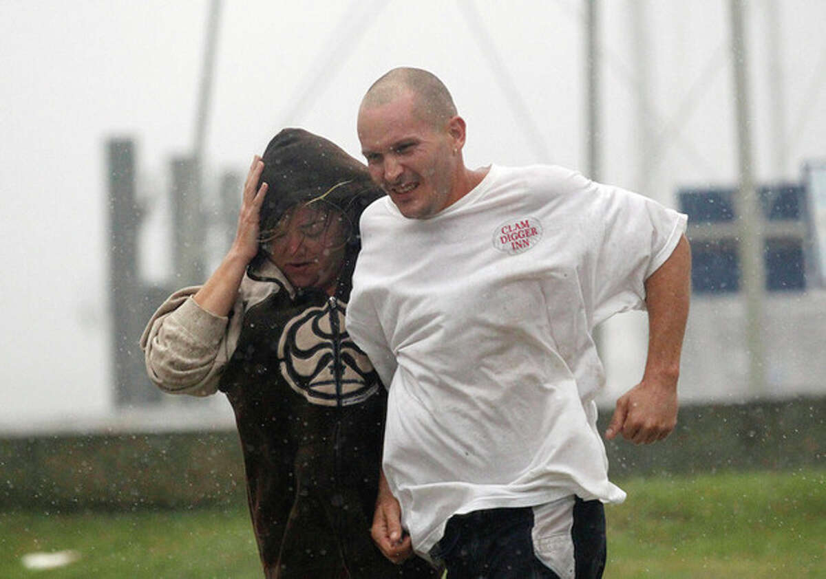 A man and a woman brace against wind and rain as Hurricane Irene approaches Saturday, Aug. 26, 2011 in Monteo, N.C. (AP Photo/John Bazemore)